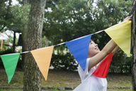 A woman in a Kyoto park holding up a colourful row of flags. - MINF02528