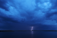 A lightning strike reflected in the water of a lake. Dark stormy dramatic sky. - MINF02669