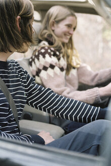 Smiling young couple driving in their car. - MINF02673