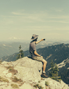 A hiker on a mountain summit, holding a smart phone, at the top of Surprise Mountain, in the Alpine Lakes Wilderness, in Mount Baker-Snoqualmie National Forest. - MINF02721