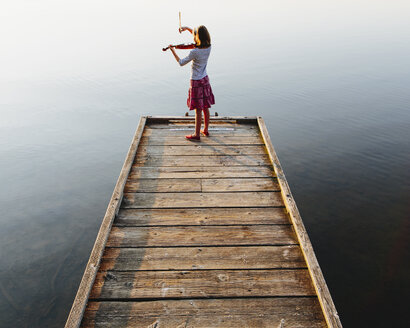 A ten year old girl playing the violin at dawn on a wooden dock. - MINF02742