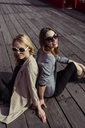 Portrait of two fashionable young women sitting on wooden floor wearing sunglasses - MAUF01528