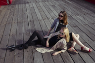 Two fashionable young women sitting on wooden floor wearing sunglasses - MAUF01531