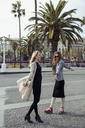 Spain, Barcelona, two fashionable young women on the street - MAUF01534