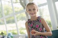 A young girl in a floral dress holding a peach fruit. - MINF02861