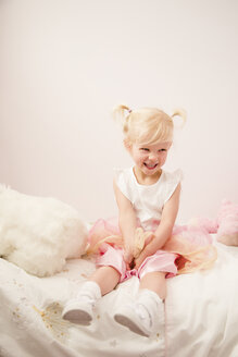 Portrait of laughing little girl sitting on bed - NMSF00203
