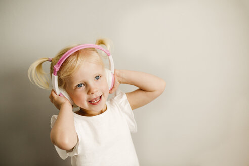 Portrait of little girl listening music with headphones dancing - NMSF00209
