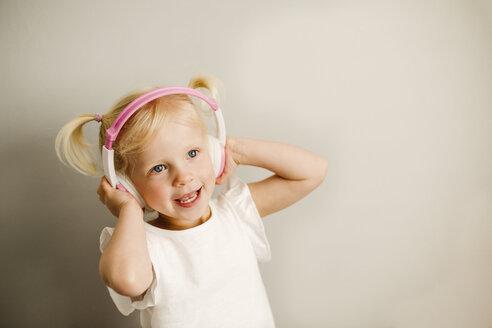 Portrait of little girl listening music with headphones dancing - NMSF00209