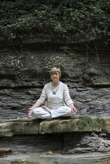 Senior woman doing yoga, meditating on rock - ALBF00582