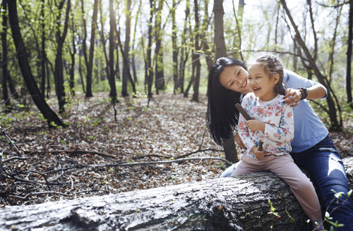Mother and daughter in park, sitting on tree trunk - AZF00019
