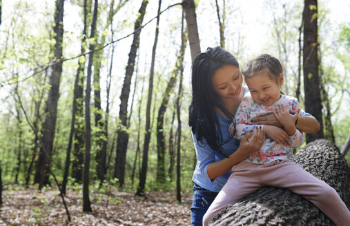 Mother and daughter in park, sitting on tree trunk - AZF00031