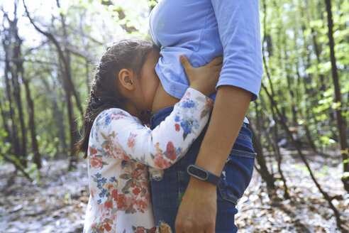 Daughter kissing mother's belly in a park - AZF00034