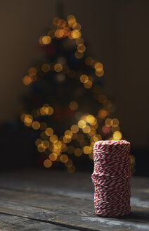 Roll of red-white packthread in front of lighted Christmas tree - AZF00046