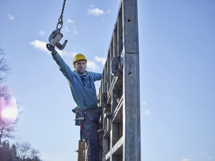 Construction worker reaching for hook of crane - CVF00993