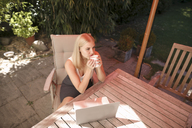 Young woman drinking coffee, laptop on garden table - KMKF00405