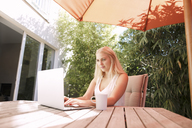 Young woman using laptop, sitting on garden table - KMKF00408