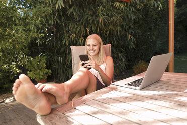 Young woman using smartphone in garden - KMKF00414