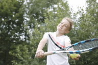 Portrait of blond boy playing tennis - KMKF00420