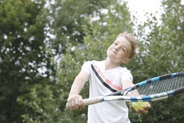 Portrait of blond boy playing tennis - KMKF00420