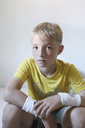Portrait of serious blond boy wearing sweatbands - KMKF00432