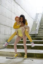 Two alternative friends having fun, wearing yellow and pink jeans clothes - AFVF01014