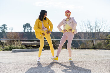 two alternative friends having fun, wearing yellow and rosa jeans clothes - AFVF01026