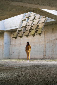 Young woman wearing yellow jeans clothes, standing in concrete building - AFVF01038