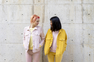 Two alternative friends having fun, wearing yellow and pink jeans clothes, face to face - AFVF01041