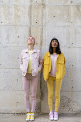 Two alternative friends having fun, wearing yellow and pink jeans clothes, looking up - AFVF01044