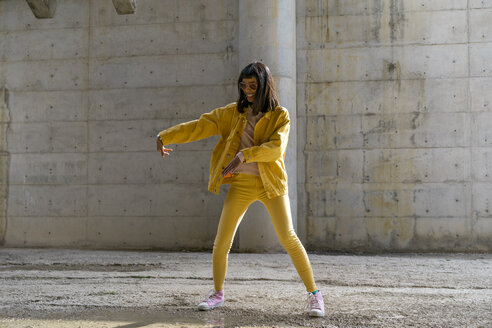 Woman wearing yellow jeans clothes, dancing - AFVF01047