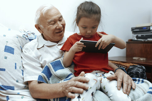 Grandfather and granddaughter with digital tablet at home - AZF00055