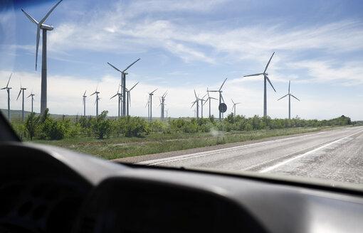 UK, Scotland, wind turbines seen from car - AZF00058