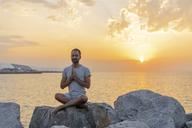 Spain. Man meditating during sunrise on rocky beach - AFVF01065