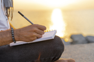 Spain. Man writing on a notebook during sunrise on rocks at the beach - AFVF01068
