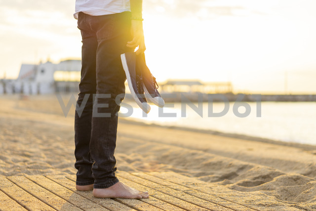Spain. Man holding shoes, at a beach during sunrise - AFVF01071