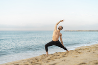 Spain. Man doing yoga on the beach in the evening - AFVF01074