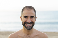 Portrait of happy man on a beach in the evening - AFVF01077