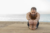 Spain. Man doing yoga on the beach in the evening, stretching legs - AFVF01080