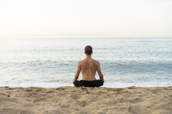 Spain. Man doing yoga on the beach in the evening, meditation, rear view - AFVF01083