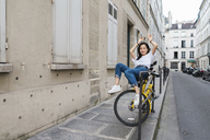 Playful young woman on bicycle at the roadside - AFVF01090
