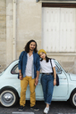 Portrait of young couple standing at small car - AFVF01096