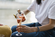 Close-up of woman pouring in sparkling blush wine - AFVF01111