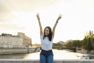 France, Paris, portrait of happy young woman at river Seine at sunset - AFVF01126