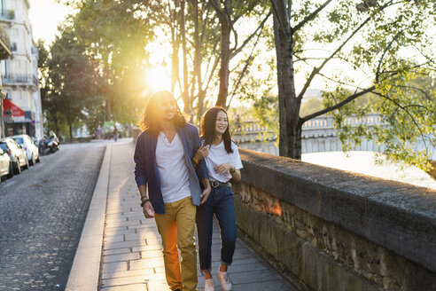 France, Paris, happy young couple walking at river Seine at sunset - AFVF01138