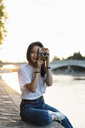 France, Paris, portrait of young woman with camera at river Seine at sunset - AFVF01147
