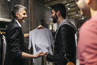 Designer in modern menswear shop offering new collection to man - JRFF01702