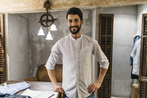 Portrait of smiling man wearing shirt in menswear shop - JRFF01708
