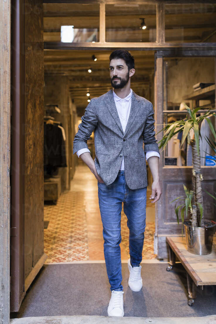 Confident man wearing jacket leaving menswear shop - JRFF01711 - Josep Rovirosa/Westend61