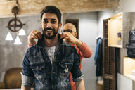 Handsome man trying on new denim jacket with stylist in modern boutique - JRFF01714