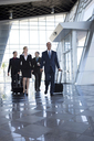 Businesspeople walking through airport with suitcases - ISF17663